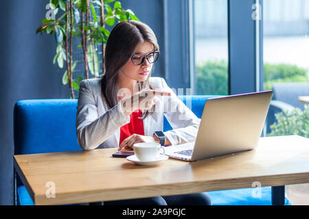 Hey you! Portrait of serious beautiful stylish brunette young woman in glasses sitting looking at her laptop screen on video call and accusing or blam - Stock Photo
