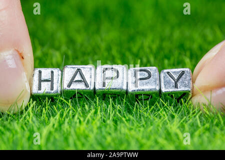 Close up on word HAPPY written in metal letters laid on grass and held between the fingers of a woman. Concept of wellness background - Stock Photo