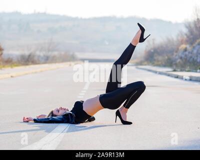 Young woman legs heels road isolated from background bokeh leg raised raising high in air effort tenseness tense posture upwards longlegs - Stock Photo