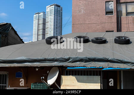 Car tires lying with on the rooftop so that the roof is not blown away by the wind. It's time to repair the roof. Leaky Roof - Stock Photo