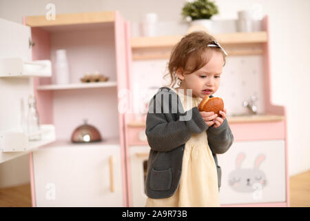 Kid and unhealthy food concept. Adorable toddler girl feeling sick when eating sweet bun in designer kitchen copy space - Stock Photo