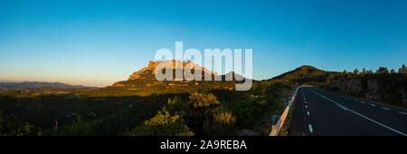 Panoramic view from a road onto the whole mountain range of Montserrat and surroundings in the warm early evening or late afternoon light. - Stock Photo