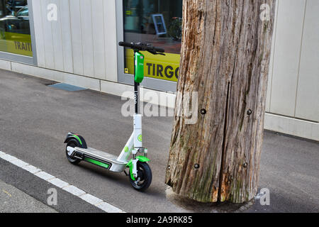 Zurich, Switzerland, 11.14.2019: Modern, electric Lime shared scooter near a trunk on the streets of Zurich - Stock Photo