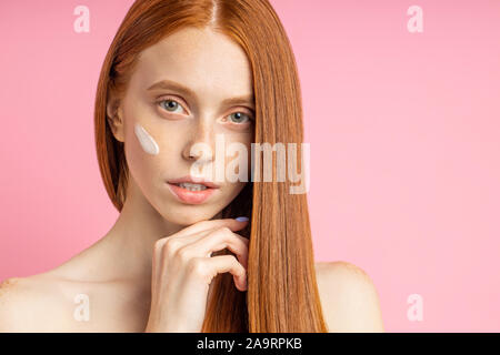 Beautiful young woman with clean perfect skin. Beauty portrait. Redhead model with bare shoulders, no makeup, applying face cream, posing against pink - Stock Photo