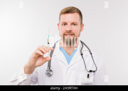 Successful young doctor with stethoscope holding syringe in front of himself - Stock Photo