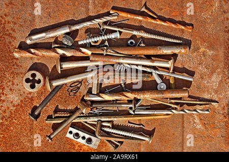 Many different steel and other metal objects on the rusty iron sheet close-up, in bright sunlight - Stock Photo