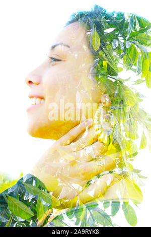 Double exposure profile portrait of a young, relaxed natural beauty large golden earrings and long brown hair combined with green tropical leaves on a - Stock Photo