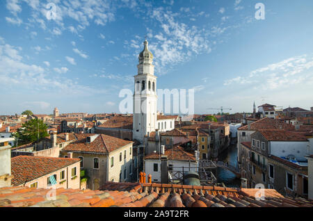 Beautiful view over the rooftops of Venice on a sunny day looking down at the canal and bridge - Stock Photo