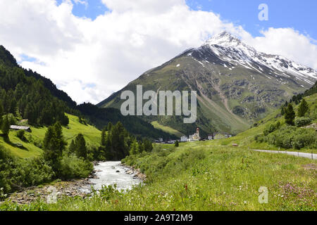 Tyrolean village with snow capped mountains, pine trees and alpine river in Austria - Stock Photo