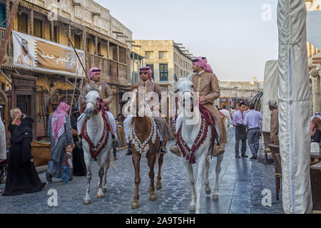 Doha-Qatar, January 24,2013: Souk Waqif in Doha Qatar main street day light view with traditional guards riding horses and people - Stock Photo
