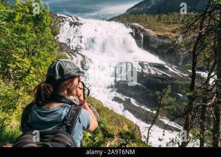 Kinsarvik, Hordaland, Norway. Young Woman Lady Tourist Traveler Taking Pictures Of Waterfall Nyastolfossen In Hardangervidda Mountain Plateau. Nyastol - Stock Photo