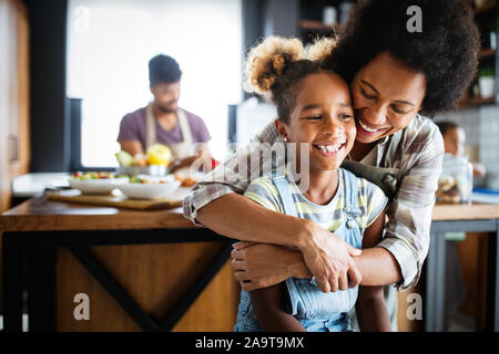 Mother and child having fun preparing healthy food in kitchen - Stock Photo