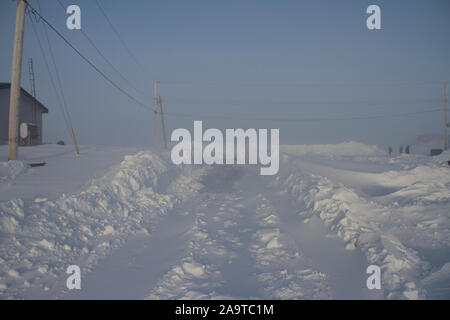 Breaking trail; a road covered in snow following a snow storm, located in Arviat, Nunavut Canada - Stock Photo