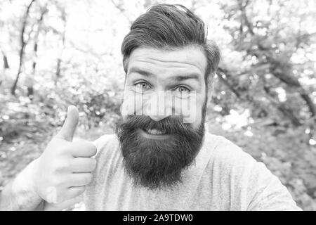 Giving his barber a thumbs up. Happy barber gesturing on natural landscape. Bearded man with shaped beard and mustache hair smiling before or after visiting barber. A barber shop for men only. - Stock Photo
