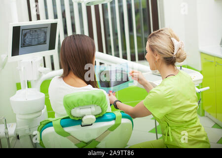 Female stomatologist in protective gloves examining patient's teeth. Dentist caries treatment at dental clinic office Stock Photo