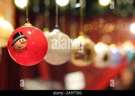 Red Christmas Bauble with a Snowman and Row of Blurred Baubles and Bokeh Festive Lights - Stock Photo