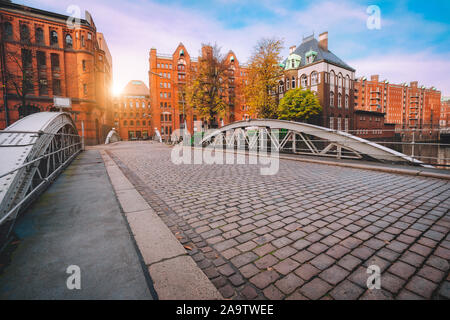 Arch bridge over canals with cobbled road in the Speicherstadt of Hamburg, Germany, Europe. Historical red brick building lit by golden sunset light n