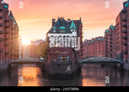 Hamburg city old port, Germany, Europe. Historical famous warehouse district with water castle palace at sunset golden light.