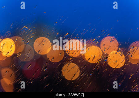 Night lights of urban traffic, wet window in rainy weather. Abstract background for banner design. Night city life, cars, weather - Stock Photo