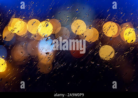 Abstract blurred colorful background. Wet window in rainy weather, bright bokeh, neon city lights - Stock Photo