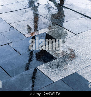 Blurry reflection shadow silhouette of people walking under umbrella in a pedestrian city wet street in a puddle, autumn rainy evening - Stock Photo