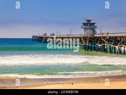 San Clemente, USA - July 03, 2017: Pacific ocean waves at the beach in a famous tourist destination in California, USA with a pier in the background - Stock Photo