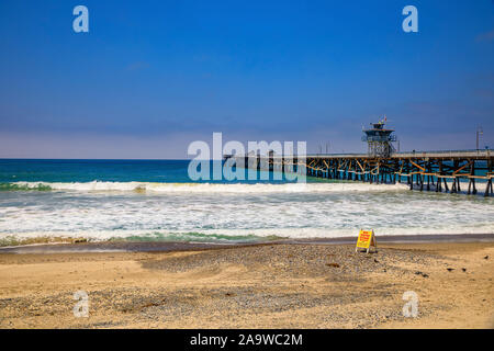 San Clemente, USA - July 03, 2017: Safety no surf warning sign on the beach in a famous California tourist destination with a pier in the background - Stock Photo