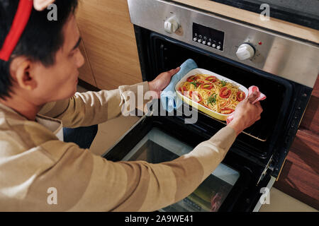 Serious man putting cooking pan with noodles and tomatoes in oven when making disch for Christmas dinner - Stock Photo