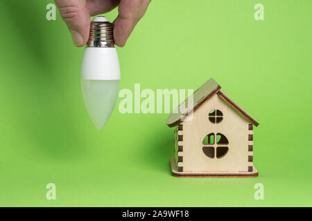 Eco power concept. LED bulb in hand and toy wooden house on green background
