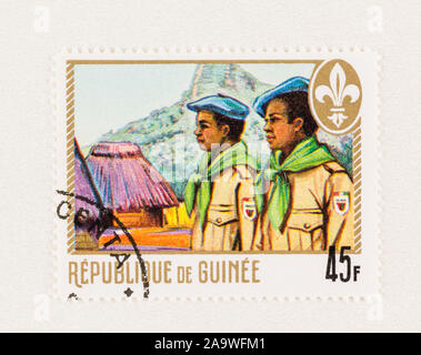SEATTLE WASHINGTON - October 5, 2019: Two boy scouts in village with grass huts on 45 F Guinee postage stamp. Scott # 539. - Stock Photo