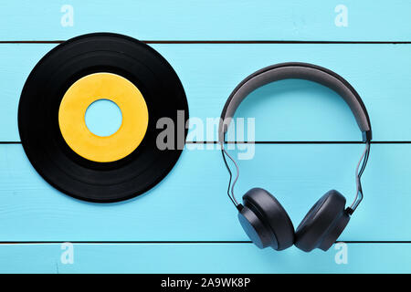 Vinyl record and a headphone on blue wooden table background. - Stock Photo