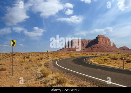 Highway in Monument Valley, Utah, USA - road curve leading towards the hills. - Stock Photo