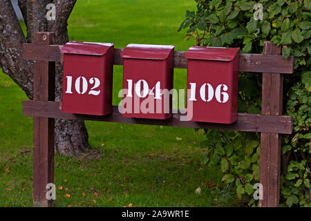 three red mailboxes in a row with white text on Roback - Stock Photo