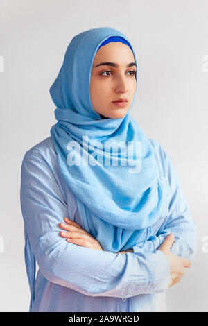 Beautiful Muslim woman in hijab against white background. Portrait of pretty middle-eastern female wearing traditional Islamic dress - abaya. Young gi - Stock Photo