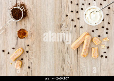 Tiramisu ingredients, ladyfingers, mascarpone, cocoa, almond liqueur and scattered black coffee beans on light brown wood background with copy space. - Stock Photo