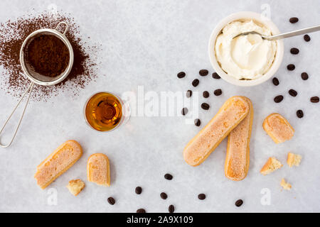 Tiramisu ingredients, ladyfingers, mascarpone, cocoa, almond liqueur and scattered black coffee beans on gray textured background with copy space. Top - Stock Photo