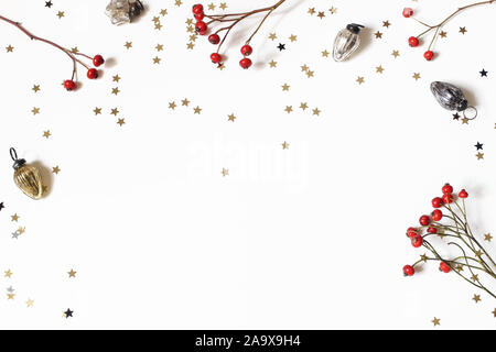 Christmas decorative frame, web banner. Red rose hips, vintage Christmas ornaments and golden confetti stars isolated on white table background - Stock Photo