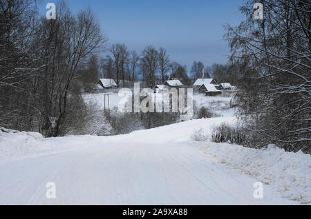 Winter landscape with road leading to village houses with snow covered roofs and smoke over chimneys - Stock Photo