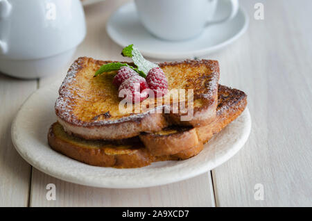 French toast, making with bread soaked in eggs and milk, then fried. Popular sweet dish served decorated with icing sugar and berries served with cup - Stock Photo