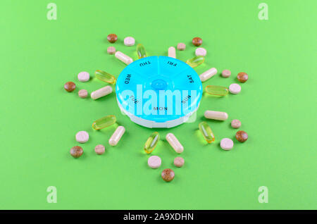 different nutritional supplements for one week and a pills box on green background - Stock Photo