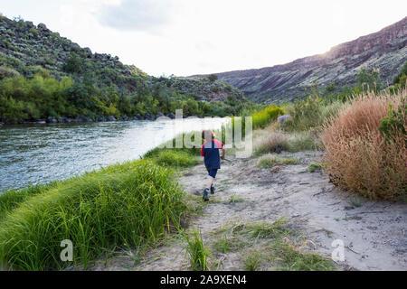 6 year old boy running along side Rio Grande River, Pilar, NM.