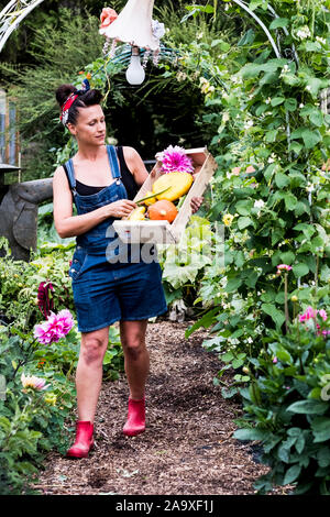 Woman walking in a garden, carrying wooden crate with fresh vegetables and flowers. - Stock Photo