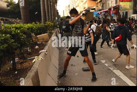 Hong Kong. 18th Nov, 2019. Protesters trying to block the main avenue, NATHAN ROAD by breaking the stone slabs acquired from the pavement.The method of civil disobedience have taken a form of 'Urban Guerrilla' as the protest continues.Nov-18, 2019 Hong Kong.ZUMA/Liau Chung-ren Credit: Liau Chung-ren/ZUMA Wire/Alamy Live News - Stock Photo