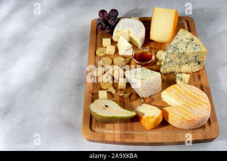 Many sorts of cheeses served on wooden board with nuts, grapes on light background. Copy space - Stock Photo
