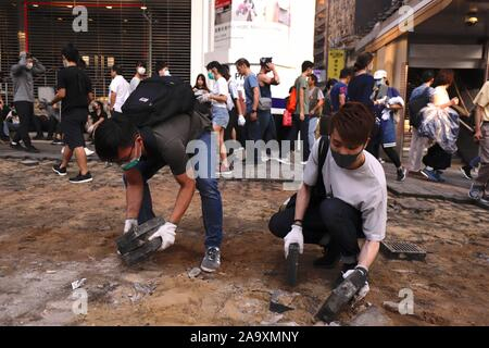 Hong Kong. 18th Nov, 2019. Protesters picks up stone slabs from the pavement in order to utilize them as obstacles to block the main avenue.Nov-18, 2019 Hong Kong.ZUMA/Liau Chung-ren Credit: Liau Chung-ren/ZUMA Wire/Alamy Live News - Stock Photo