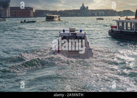 Venice, Italy Carabinieri Police Boat on the lagoon. Evening view of Patrol Boat with Italian flag sailing at the Venetian lagoon on Saint Mark area. - Stock Photo