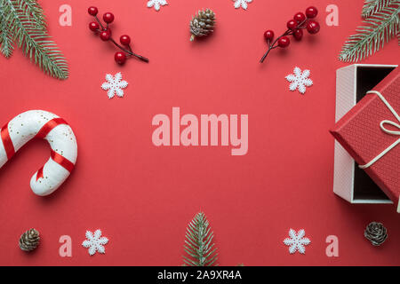 Christmas frame made of fir branches, red berries, snowflakes, candy cane, gift box and pine cones on red background. Christmas background. Flat lay. - Stock Photo