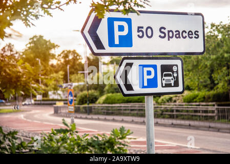 Directional signs along a street indicaticating a car park with a charger station for electric vehicles - Stock Photo