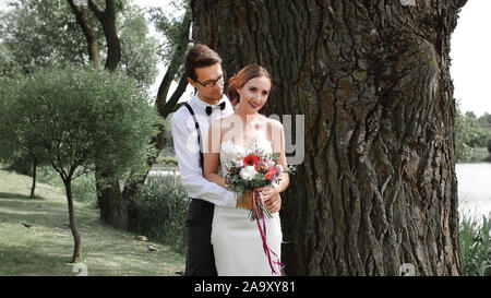 happy bride and groom standing near a big tree - Stock Photo