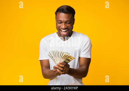 Happy Afro Man Holding Money Standing Over Yellow Studio Background - Stock Photo